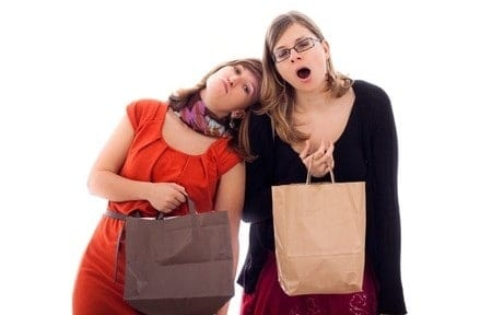 Two young women tired of shopping, isolated on white background